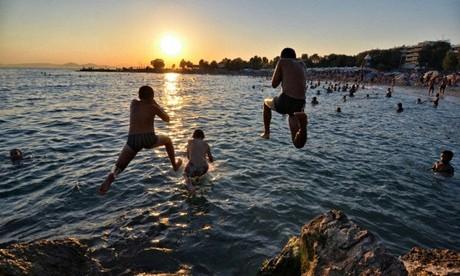Young Greeks jumping from rocks near Glyfada