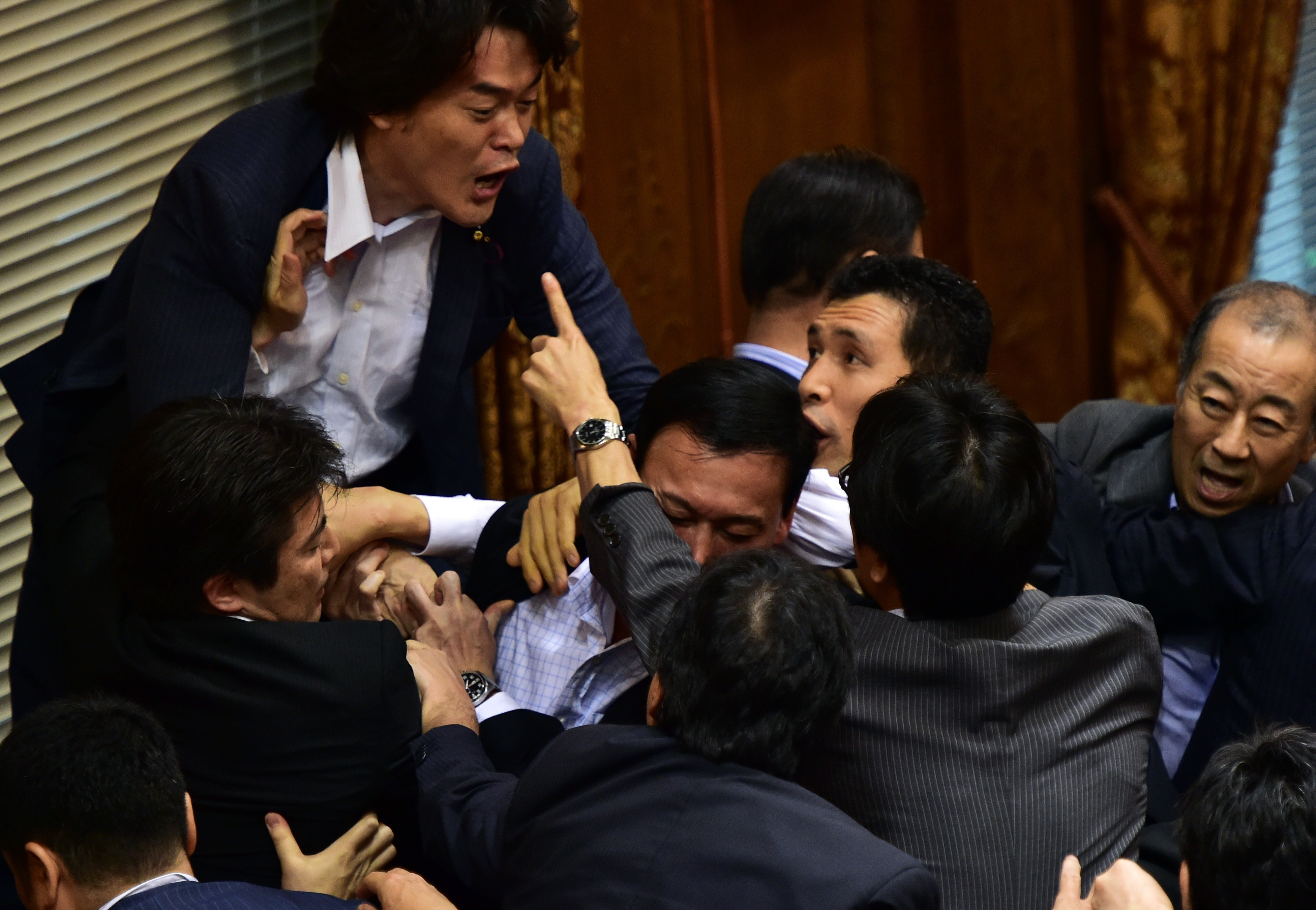 Japanese ruling and opposition lawmakers scuffle at the Upper House's ad hoc committee session for the controversial security bills at the National Diet in Tokyo on September 17, 2015. Japanese lawmakers came to blows as they tried -- and failed -- to stop the passage of a security bill that could see the military fight abroad for the first time in decades.  AFP PHOTO / Yoshikazu TSUNO
