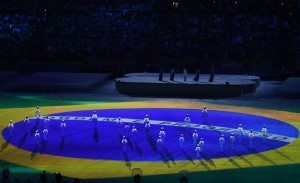 Brazil's national flag is projected onto the playing field as singers perform the country's national anthem during the closing ceremony of the Rio 2016 Olympic Games at the Maracana stadium in Rio de Janeiro on August 21, 2016. / AFP PHOTO / Greg BAKER
