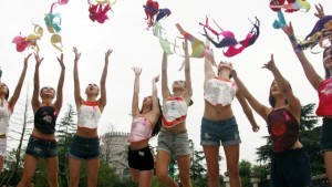 HANGZHOU, CHINA - JUNE 22: (CHINA OUT) Pink Ribbon volunteers throw up bras to raise women's attention on breast health on a public service activity at Song Dynasty Town on June 22, 2015 in Hangzhou, Zhejiang Province of China. Families of breast cancer patients from Zhejiang, Yunnan, Hainan, Sichuan province received donations on the public service activity held by China Fenhong Sidai Breast Cancer Foundation and Song Dynasty Town. (Photo by ChinaFotoPress/ChinaFotoPress via Getty Images)