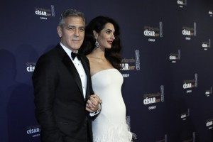 US actor George Clooney (L) and his wife British-Lebanese lawyer Amal Clooney pose as they arrive for the 42nd edition of the Cesar Ceremony at the Salle Pleyel in Paris on February 24, 2017. / AFP PHOTO / THOMAS SAMSON