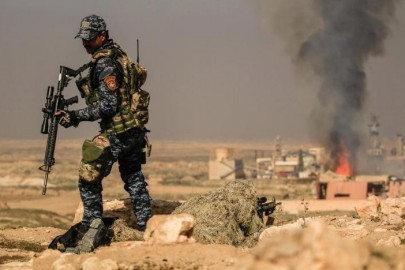 Smoke rises  from  sugar factory as Iraqi security forces sniper  aim his weapon toward Mosul's airport  during a battle  with islamic state's militants south west Mosul, Iraq February 23, 2017. REUTERS/Zohra Bensemra
