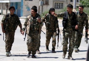 FILE PHOTO - Kurdish fighters from the People's Protection Units (YPG) walk along a street in the southeast of Qamishli city, Syria, April 22, 2016. REUTERS/Rodi Said/File Photo