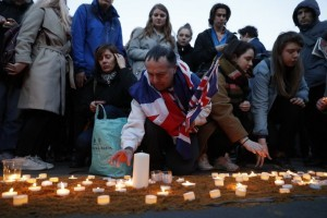 People including a man draped in the Union Flag, John Loughrey (C), light candles on a patch of sand during a vigil in Trafalgar Square in central London on March 23, 2017 in solidarity with the victims of the March 22 terror attack at the British parliament and on Westminster Bridge.  Britain's parliament reopened on Thursday with a minute's silence in a gesture of defiance a day after an attacker sowed terror in the heart of Westminster, killing three people before being shot dead. Sombre-looking lawmakers in a packed House of Commons chamber bowed their heads and police officers also marked the silence standing outside the headquarters of London's Metropolitan Police nearby.  / AFP PHOTO / Adrian DENNIS