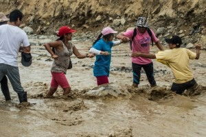 Local residents try to cross a flash flood in Huachipa district, on the east side of Lima, on March 19, 2017.  El Nino-fuelled flash floods and landslides hit parts of Lima, where most of the water distribution systems have collapsed due to unusual heavy seasonal downpours and people are facing drinking water shortages. / AFP PHOTO / ERNESTO BENAVIDES