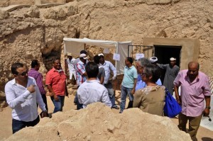 Journalists and members of an Egyptian archaeological team stand near artifacts discovered in a 3,500-year-old tomb in the Draa Abul Nagaa necropolis, near the southern city of Luxor, on April 18, 2017. Egyptian archaeologists have discovered six mummies, colourful wooden coffins and more than 1,000 funerary statues in the 3,500-year-old tomb, the antiquities ministry said. / AFP PHOTO / STRINGER