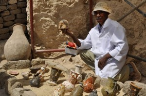 A member of an Egyptian archaeological team shows artifacts discovered in a 3,500-year-old tomb in the Draa Abul Nagaa necropolis, near the southern city of Luxor, on April 18, 2017. Egyptian archaeologists have discovered six mummies, colourful wooden coffins and more than 1,000 funerary statues in the 3,500-year-old tomb, the antiquities ministry said. / AFP PHOTO / STRINGER