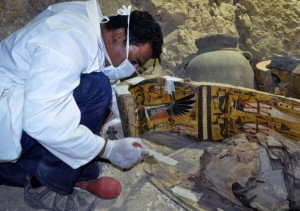 A member of an Egyptian archaeological team works on a wooden coffin discovered in a 3,500-year-old tomb in the Draa Abul Nagaa necropolis, near the southern Egyptian city of Luxor, on April 18, 2017. Egyptian archaeologists have discovered six mummies, colourful wooden coffins and more than 1,000 funerary statues in the 3,500-year-old tomb, the antiquities ministry said. / AFP PHOTO / STRINGER