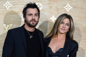 US actor Justin Theroux (L) and his wife US actress Jennifer Aniston (R) pose during a photocall ahead of a diner for the launch of a Louis Vuitton leather goods collection in collaboration with US artist Jeff Koons, at the Louvre in Paris on April 11, 2017. / AFP PHOTO / GABRIEL BOUYS