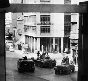 "Greek army tanks and soldiers take position in Omnia Place, 27 April 1967, after the military coup of 4 colonels of the Greek army. On 21 April 1967, a group of right-wing army officers led by Brigadier Stylianos Pattakos and Colonels Georgios Papadopoulos and Nikolaos Makarezos seized power in a coup d'etat and installed a military junta, also called ""The Regime of the Colonels"", that ended in 1974. / AFP PHOTO / VOTAVA / -"