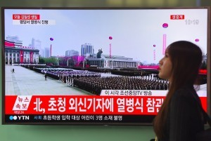 A woman walks past a television screen broadcasting live footage of a ceremony to mark the 105th anniversary of the birth of North Korea's founder Kim Il-Sung, at a railway station in Seoul on April 15, 2017. North Korea's military forces were massed in Pyongyang on April 15 for a show of strength by leader Kim Jong-Un as tensions mount over his nuclear ambitions. / AFP PHOTO / JUNG Yeon-Je