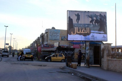 """People walk under a billboard erected by the Islamic State (IS) group as part of a campaign in the IS controlled Syrian city of Raqqa on November 2, 2014. Arabic writting on billboard """"Now.. now.. the fight has come"""".  AFP PHOTO/RMC/STR / AFP PHOTO / Raqa Media Center / -"""