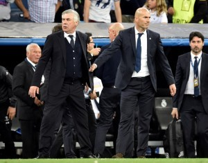 Bayern Munich's Italian head coach Carlo Ancelotti (L) stands beside  Real Madrid's French coach Zinedine Zidane after during the UEFA Champions League quarter-final second leg football match Real Madrid vs FC Bayern Munich at the Santiago Bernabeu stadium in Madrid in Madrid on April 18, 2017. / AFP PHOTO / GERARD JULIEN