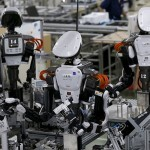 Humanoid robots work side by side with employees in the assembly line at a factory of Glory Ltd., a manufacturer of automatic change dispensers, in Kazo, north of Tokyo, Japan, July 1, 2015. Japanese firms are ramping up spending on robotics and automation, responding at last to premier Shinzo Abe's efforts to stimulate the economy and end two decades of stagnation and deflation. Picture taken July 1, 2015. REUTERS/Issei Kato  - RTX1IU6W