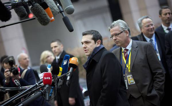 Greek Prime Minister Alexis Tsipras, center, speaks with the media as he arrives for an EU summit in Brussels on Thursday, Feb. 12, 2015. European Union leaders on Thursday said the full respect of the planned weekend cease-fire in eastern Ukraine will be essential before there could be a change in the sanctions regime imposed on Moscow. (ANSA/AP Photo/Virginia Mayo)