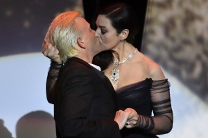 Italian actress and master of ceremonies Monica Bellucci (R) and French comedian Alex Lutz kiss as they perform on stage on May 17, 2017 during of the opening ceremony of the 70th edition of the Cannes Film Festival in Cannes, southern France.  / AFP PHOTO / Alberto PIZZOLI