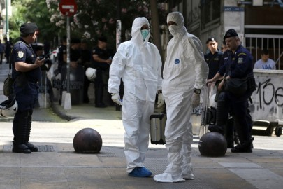 Police bomb disposal experts in white clothes, search for evidence, next to the central Athens offices of the Pan-Hellenic Socialist Movement, or Pasok party, in central Athens, on Sunday, May 25, 2014 . Two shots from an AK-47 assault rifle were fired against the socialist PASOK party headquarters early Sunday. No one was at the premises at the time and there were no injuries. Greeks vote Sunday for  European Parliament and a second-round voting in local government polls. (AP Photo/Dimitris Messinis)