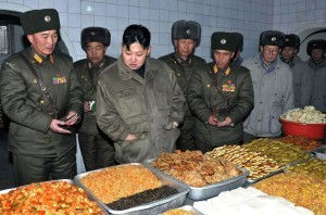 In this undated photo released by the Korean Central News Agency and distributed in Tokyo by the Korea News Service on Thursday, Jan. 19, 2012, North Korean leader Kim Jong Un, center, looks at food items at an undisclosed location in North Korea. KCNA reported he was inspecting a military unit. (AP Photo/Korean Central News Agency via Korea News Service) JAPAN OUT UNTIL 14 DAYS AFTER THE DAY OF TRANSMISSION