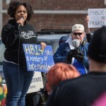 Chanelle Helm, a Black Lives Matter of Louisville organizer, speaks near Indivisible Kentucky's Save My Care Bus. Groups protest The Republican Party's proposed changes to the Affordable Care Act during a visit by Vice President Mike Pence with Kentucky Governor Matt Bevin and business leaders Saturday, March 11, 2017 at Trane Parts and Distribution Center, 12850 Plantside Drive, Louisville, Ky. (Photo by Brian Bohannon)