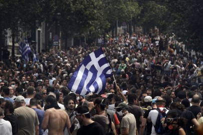Greek protesters, one waving a national flag, gather in Athens, Wednesday, June 15, 2011. Hundreds of protesters clashed with riot police in central Athens Wednesday as a major anti-austerity rally degenerated into violence outside Parliament, where the struggling government was to seek support for new cutbacks to avoid a disastrous default. (AP Photo/Kostas Tsironis)