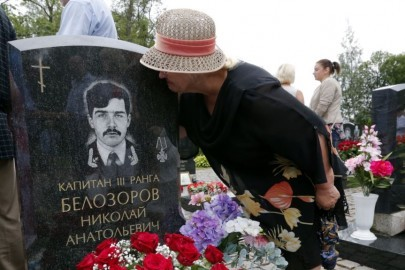 epa04350458 A relative of 3rd rank Captain Nikolai Belosorov kisses his tombstone at the Serafimovskoye cemetery during the memorial ceremony on the 14th anniversary of the Kursk submarine tragedy, in St. Petersburg, Russia, 12 August 2014. Nuclear submarine 'Kursk' sank in Barents Sea taking the lives of 118 sailors on 12 August 2000.  EPA/ANATOLY MALTSEV