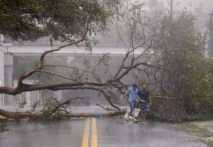 epa06197198 Men walk through toppled trees along Brickell Avenue after the full effects of Hurricane Irma struck in Miami, Florida, USA, 10 September 2017. Many areas are under mandatory evacuation orders as Irma Florida.  EPA/ERIK S. LESSER