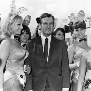 Playboy editor and tycoon Hugh Hefner is greeted by a group of bunny girls from his Playboy Clubs, upon his arrival at London Airport.   (Photo by Dove/Getty Images)