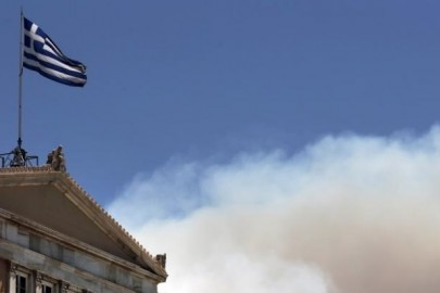 A Greek national flag flutters atop the parliament building as smoke from a raging wildfire rises in Athens, Greece July 17, 2015. REUTERS/Alkis Konstantinidis