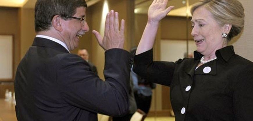 U.S. Secretary of State Hillary Clinton gives Turkey's Foreign Minister Ahmet Davutoglu a high five at the start of their bilateral meeting at the Emirates Palace Hotel in Abu Dhabi June 9, 2011.   REUTERS/Susan Walsh/Pool   (UNITED ARAB EMIRATES - Tags: POLITICS)