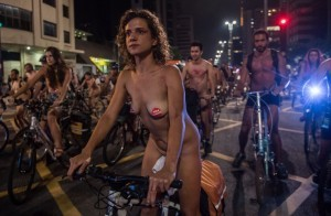 Naked cyclists ride their bikes along Paulista Avenue in Sao Paulo, Brazil, to demand better condition of the city roads and to raise awareness on the safety of cyclists and reducing oil dependence, as part of the World Naked Bike Ride (WNBR) international movement, on March 10, 2018. / AFP PHOTO / Nelson ALMEIDA