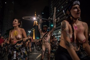 Naked cyclists demonstrate along Paulista Avenue in Sao Paulo, Brazil, to demand better condition of the city roads and to raise awareness on the safety of cyclists and reducing oil dependence, as part of the World Naked Bike Ride (WNBR) international movement, on March 10, 2018. / AFP PHOTO / Nelson ALMEIDA