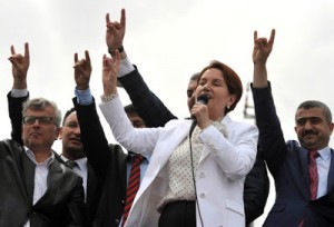 Former Turkish Interior minister and lawmaker of Turkey's right-wing Nationalist Movement Party (MHP) Meral Aksener (C) speaks to supporters as riot police sealed off a hotel to prevent thousands of MHP dissidents from holding a party congress in Ankara, on May 15, 2016. Members of the MHP party were prevented from holding a congress on May 15 aimed at unseating longtime leader Devlet Bahceli and recovering ground lost to President Recep Tayyip Erdogan's party. Dissidents from the Nationalist Movement Party launched a campaign to oust Bahceli after a general election in November in which the party shed half its support -- taking just 40 seats in the 550-member parliament compared to 80 five months previously. / AFP PHOTO / ADEM ALTAN