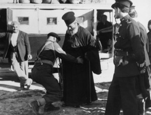 6th December 1955:  British soldiers search a Greek orthodox priest, one of the passengers on a bus being checked after a local post office was damaged by fire.  (Photo by Central Press/Getty Images)