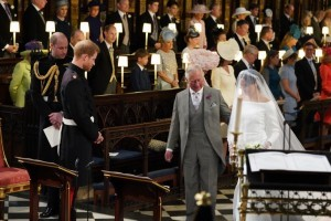 Britain's Prince Harry, Duke of Sussex (2nd L), looks at his bride, Meghan Markle, as she arrives accompanied by the Britain's Prince Charles, Prince of Wales in St George's Chapel during the wedding ceremony of Britain's Prince Harry, Duke of Sussex and US actress Meghan Markle in St George's Chapel, Windsor Castle, in Windsor, on May 19, 2018. / AFP PHOTO / POOL / Jonathan Brady