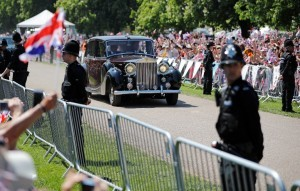 Well-wishers wave flags as Meghan Markle is driven towards Windsor Castle on the Long Walk leading ahead of the wedding and carriage procession of Britain's Prince Harry, Duke of Sussex and Meghan Markle in Windsor, on May 19, 2018. / AFP PHOTO / Tolga AKMEN
