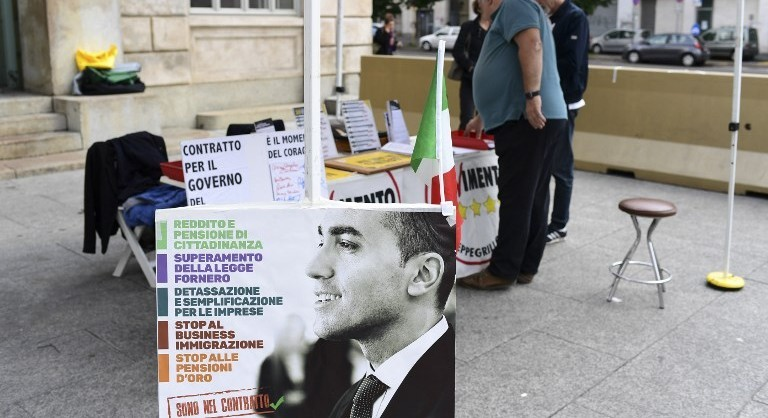 Supporters of anti-establishment Five Star Movement (M5S) hold a stand to communicate on a proposal of common governmental program with far-right League party (Lega), in center Milan, on May 20, 2018. The anti-establishment Five Star Movement (M5S) and far-right League party should meet Italy's President Sergio Mattarella tomorrow in Rome and reveal the name of their Prime Minister. / AFP PHOTO / MIGUEL MEDINA