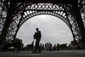 French soldier patrols during a press visit of the new security barriers under construction around the Eiffel Tower in Paris, France, Thursday, June 14, 2018. Paris authorities have started replacing the metal security fencing around the Eiffel Tower with a more visually appealing glass wall. The company operating the monument said see-through panels are being set up instead of the fences at the north and south of the famed monument that were installed for the Euro 2016 soccer event. Each panel is 3 meters high, over 6 centimeters thick and weighs 1.5 ton. (AP Photo/Francois Mori)