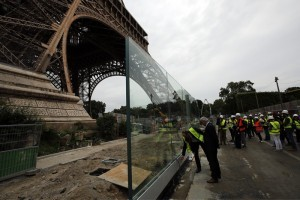 Bernard Gaudillere, president of the SETE, Eiffel Tower Exploitation Society, second left, stands in front of a new security bulletproof glass barrier under construction around the Eiffel Tower in Paris, France, Thursday, June 14, 2018. Paris authorities have started replacing the metal security fencing around the Eiffel Tower with a more visually appealing glass wall. The company operating the monument said see-through panels are being set up instead of the fences at the north and south of the famed monument that were installed for the Euro 2016 soccer event. Each panel is 3 meters high, over 6 centimeters thick and weighs 1.5 ton. (AP Photo/Francois Mori)