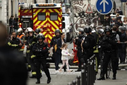 epa06802681 A woman and a young girl (C) are evacuated by police forces during a hostage taking situation in Rue des Petites Ecuries, in Paris, France, 12 June 2018. An armed man carrying a bomb and handgun is allegedly holding two hostages, according to some reports.  EPA/YOAN VALAT